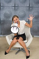 A woman yelling in a megaphone in an office, Sweden.