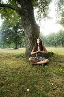 Young woman holding her hands against her chest and meditating in nature  Taken in Lipica, Slovenia  Concept: teenagers and nature, spiritual teenager...