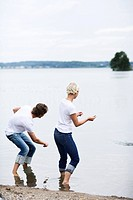 A man and a woman throwing pebbles trying to make them bounce on the surface of the water, Sweden.