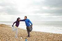 Couple stretching on beach on cloudy day
