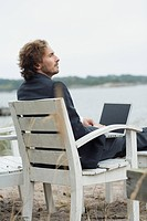 A man with a computer on the beach, Sweden.
