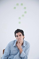 Man thinking with post_it note question makr behind him