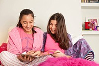 girls reading magazine on bed