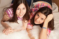 teenage girls smiling , lying on pillows