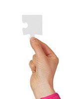 Female hand holding a puzzle piece on a white background