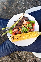 Plate with salad and corn cob