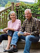 Senior couple sitting on steps, having coffee, smiling, portrait