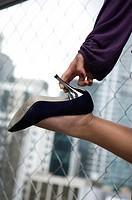 Hand holding high heel shoe