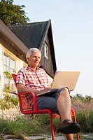 Man using laptop in front of house