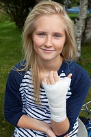 Teenage girl with bandage on hand, smiling, portrait