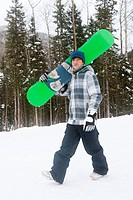 Mixed race snowboarder carrying snowboard
