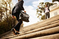 Businesswoman walking up stairs toward co_worker