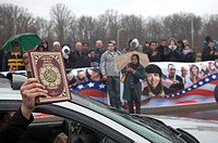Dearborn, Michigan - A passenger in a passing car holds up a copy of the Quran to cheers from a crowd of mostly young Arab-Americans gathered outside ...