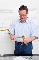 Architekt faltet in seinem Büro einen Zollstock auseinander