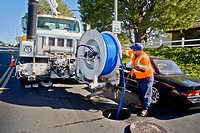 Using a truck mounted suction system, a technician cleans a clogged sewer in Laguna Niguel, CA  Note high visibility safety vest