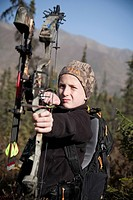 Young boy aims with a compound bow while bow hunting in a Black Spruce forest in the Eklutna Lake area, Chugach Mountains, Chugach State Park, Southce...