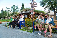 Visitors sit on a bench in front of the log cabin Visitor Center and milepost sign in downtown Anchorage, Southcentral Alaska, Summer
