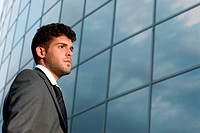 Young businessman looking to good future on modern building background