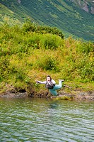 Humorous view of a fly fisherwoman falling into a lake with flyrod still in hand, Kenai Peninsula, Southcentral Alaska, Summer