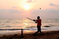 Playing cricket, the national sport of India, on Anjuna Beach at sunsetGoa State, India, Asia.
