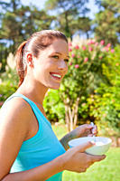Close_up of smiling young woman holding bowl and looking away