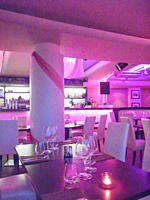 Interior of empty beautiful restaurant illuminated with purple light