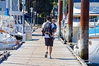 a father holding his young son as he walks down a pier in a marina, victoria, british columbia, canada