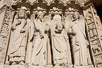 the statues around st. denis holding his head at the notre_dame cathedral, paris, france