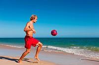 Mann am Strand kickt den Fußball