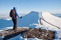 Female hiker viewing Pen Y Fan from Summit of Corn Du in winter, Brecon Beacons national park, Wales