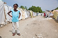 a girl stands by a row of tents made of bed sheets and plastic which are now home for many haitian families, port_au_prince, haiti