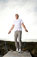 Mature man skipping rope on jetty