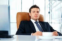 Young business executive sitting relaxed in chair looking at you