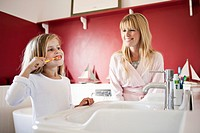 Woman watching daughter brush her teeth (thumbnail)