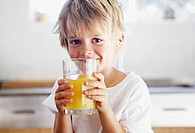 Boy holding a glass of orange juice