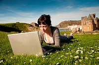 A young woman UK Aberystwyth university student working on her apple laptop computer outdoors on a sunny warm day