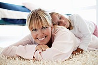 Mother and daughter lying on floor