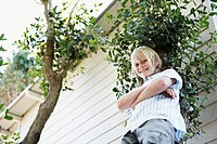 Boy leaning against tree by house