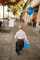 Blond boy walking down street with balloon