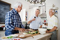 Three senior men preparing food in kitchen