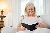 Senior woman sitting in armchair, reading book