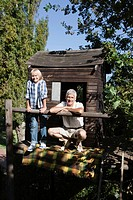 Boy 10_12 with grandfather posing by tree house