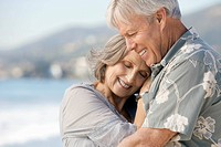 Happy senior couple hugging on beach (thumbnail)