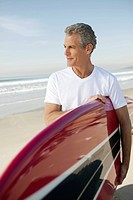 Male surfer carrying surfboard on beach (thumbnail)