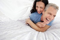 Playful couple lying on bed (thumbnail)