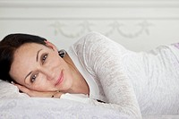 Portrait of smiling woman lying on bed