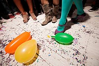 People dancing at party with balloons on floorboards