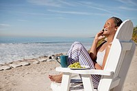 Woman talking on mobile phone and laughing on beach
