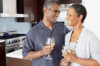Happy couple holding wineglasses in kitchen