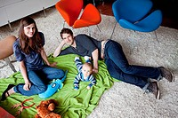 Portrait of parents with baby son sitting on floor in living room (thumbnail)